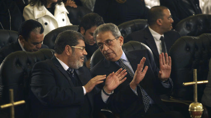 FILE - In this Friday, Jan. 6, 2012 file photo, Mohamed Morsi, left, of Egypt's Muslim Brotherhood and Egyptian presidential hopeful Amr Moussa, right, talk before Christmas Eve mass, led by Coptic Pope Shenouda III at the Coptic cathedral in Cairo, Egypt. In the race to become the first president of the new Egypt, the secular candidate with the strongest chance of beating increasingly powerful Islamists has to overcome the baggage he brings from the old Egypt. On the campaign trail ahead of next month's landmark vote, the 76-year-old Amr Moussa presents himself as an elder statesman with years of experience in politics and government, first from a decade as foreign minister under former President Hosni Mubarak, then from another decade leading the Arab League. (AP Photo/Maya Alleruzzo, File)