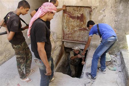 A Free Syrian Army fighter helps a fellow fighter get out of a tunnel in the old city of Aleppo