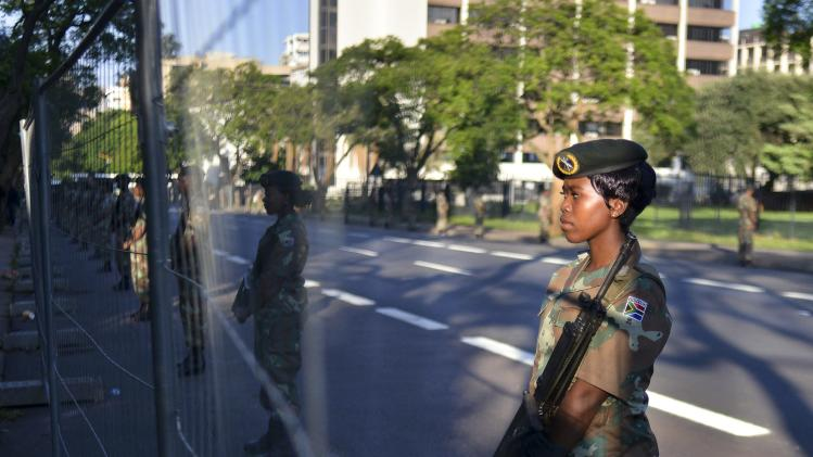 Members of the SANDF guard the route that a hearse carrying the coffin of former South African President Mandela will travel on, in Pretoria