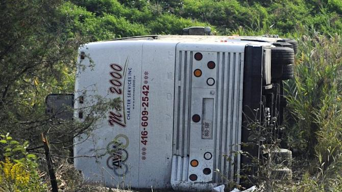 A bus sits in a ditch after it overturned at an exit ramp off Route 80 in Wayne, N.J. Saturday, Oct. 6, 2012. The chartered tour bus from Toronto carrying about 60 people overturned on an interstate exit ramp. Three people have been taken to hospital with non-life-threatening injuries. (AP Photo/Bill Kostroun)