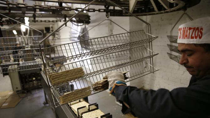 Edwin Caballeros loads fresh baked matzos into a packaging machine at the Streit's matzo factory in New York, Wednesday, March 4, 2015. (AP Photo/Seth Wenig)