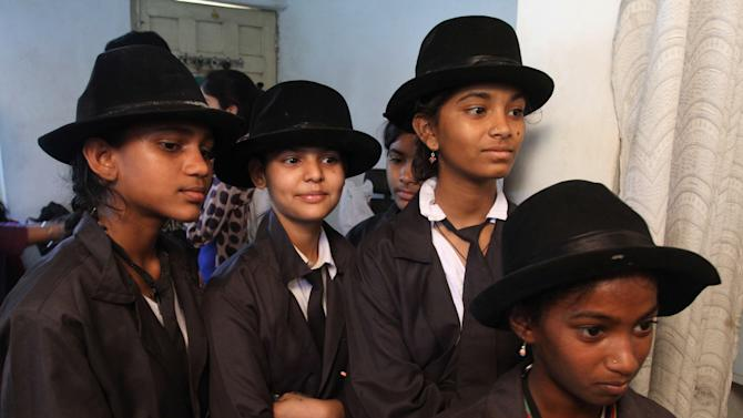 Indian girls wait for their turn to be made up to look like Charlie Chaplin to participate in the annual parade to celebrate his birthday in Adipur, Gujarat state, India, Tuesday, April 16, 2013. Canes in hand and bowler hats firmly in place, dozens of Charlie Chaplin impersonators tramped through the streets of this small port town in western India on Tuesday to celebrate the birthday of the legendary comic actor and filmmaker. (AP Photo/Ajit Solanki)