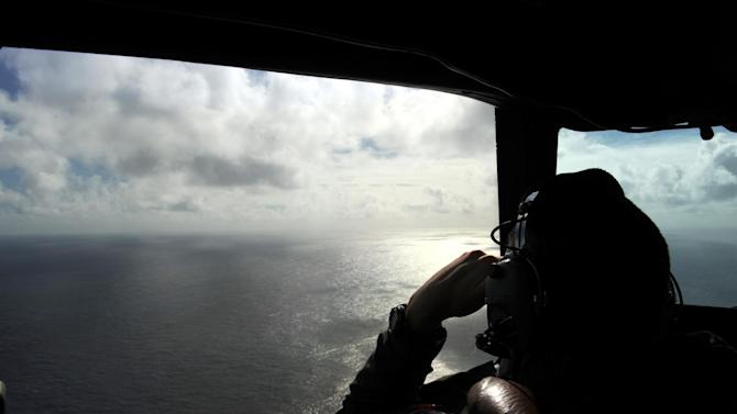 FILE - In this April 13, 2014 file photo taken from the Royal New Zealand air force (RNZAF) P-3K2-Orion aircraft, pilot and aircraft captain, Flight Lt. Timothy McAlevey looks out of a window while searching for debris from missing Malaysia Airlines Flight 370, over the Indian Ocean off the coast of western Australia. Australia, Indonesia and Malaysia will lead a trial to enhance the tracking of the aircraft over remote oceans, allowing planes to be more easily found should they vanish like Malaysia Airlines Flight 370, Australia's transport minister said Sunday, March 1, 2015. The announcement comes one week ahead of the anniversary of the disappearance of the flight, which vanished in 2104 on a flight from Kuala Lumpur to Beijing with 239 people on board. No trace of the plane has been found. (AP Photo/Greg Wood, Pool, File)