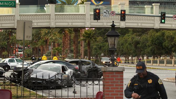 Law enforcement personal investigate a mulit-vehicle accident on Las Vegas Blvd. and Flamingo Road Thursday, Feb. 21, 2013.  Authorities say a Range Rover opened fire on a Maserati at a stoplight, sending it crashing into a taxi that went up in flames, leaving three people dead and at least six injured. Police were checking with nearby businesses to see whether a previous altercation prompted the car-to-car attack  (AP Photo/Las Vegas Review-Journal, Jeff Scheid) LOCAL TV OUT; LOCAL INTERNET OUT; LAS VEGAS SUN OUT