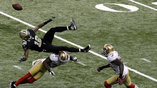 New Orleans Saints wide receiver Marques Colston (12) is upended by San Francisco 49ers strong safety Donte Whitner (31), causing an interception returned for a touchdown, in the second half of an NFL football game in New Orleans, Sunday, Nov. 25, 2012. (AP Photo/Bill Haber)