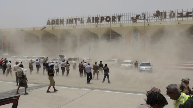 People seek cover from rising dust as a Qatari military cargo plane carrying aid lands at the international airport of Yemen's southern port city of Aden