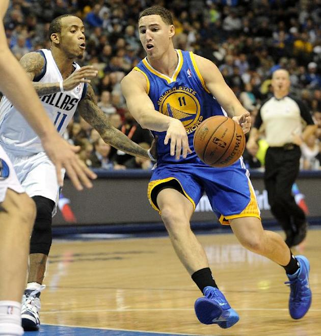 Golden State Warriors shooting guard Klay Thompson, right, drives on Dallas Mavericks shooting guard Monta Ellis, left, in the second half during an NBA basketball game on Wednesday, Nov. 27, 2013, in