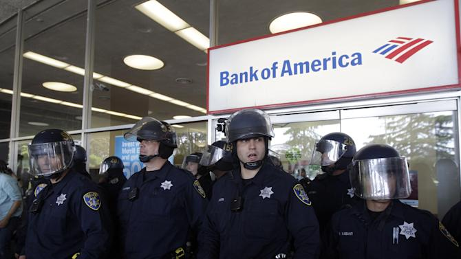 FILE - In this May 1, 2012 file photo, Oakland police officers guard a Bank of America branch during May Day protests in Oakland, Calif. The chaotic scene recalls several earlier clashes between Occupy protesters and Oakland police. The city of Oakland took a big risk this year when it decided to borrow nearly $213 million to cover pensions owed to its retired police and firefighters. Rather than laying off more staff or reducing library services, leaders in this Northern California port city are betting that the stock market will improve.(AP Photo/Marcio Jose Sanchez, file)