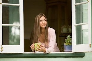 woman having coffee looking out of window