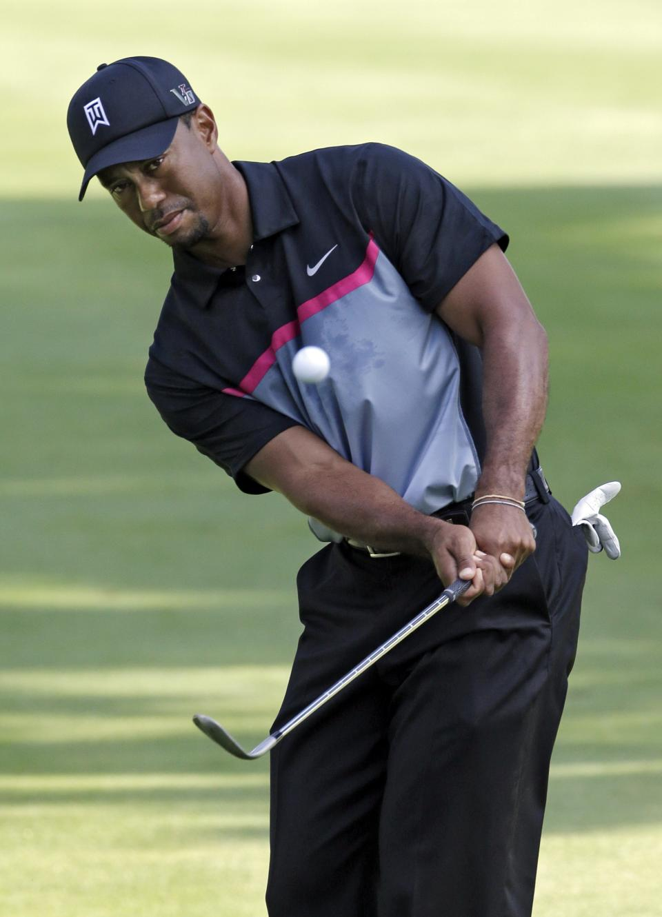 Tiger Woods chips to the 11th green during the first round of the Bridgestone Invitational golf tournament Thursday, Aug. 1, 2013 at Firestone Country Club in Akron, Ohio. (AP Photo/Mark Duncan)