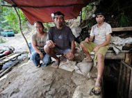 Small-scale miner Reynaldo Elejorde (C) with his wife and son at the mouth of the mine tunnel on Mount Diwata on the southern Philippine island of Mindanao. The government's small-scale mining provisions were originally intended to give poor, mainly rural people a chance to earn a little money