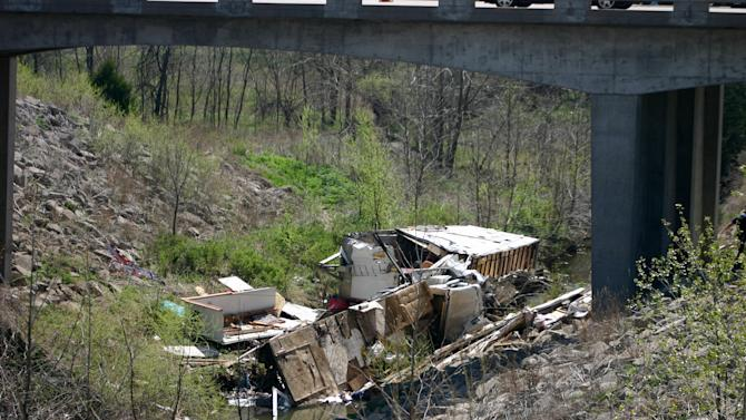 In a Sunday, April 1, 2012 photo, the wreckage of a box truck that was pulling a trailer lies in a ravine after it hit a guardrail and a concrete bridge, near Williamsburg, Kan. Authorities said 18 people were inside the vehicle, which had living quarters inside, when it crashed, killing five. A family friend said a Minnesota family and some friends were taking a spring break vacation to see a motocross race.  (AP Photo/The Ottawa Herald, Jeanny Sharp) NO SALES