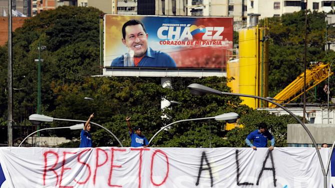 "University students hang a banner that reads in Spanish: ""Respect the constitution,"" over the side of a bridge near a billboard showing President Hugo Chavez in Caracas, Venezuela, Wednesday, Jan. 16, 2013. Vice President Nicolas Maduro took the place of the ailing Venezuelan president on Tuesday by delivering a short speech and turning in a state-of-the-nation report amid legal debate about his legitimacy. (AP Photo/Fernando Llano)"
