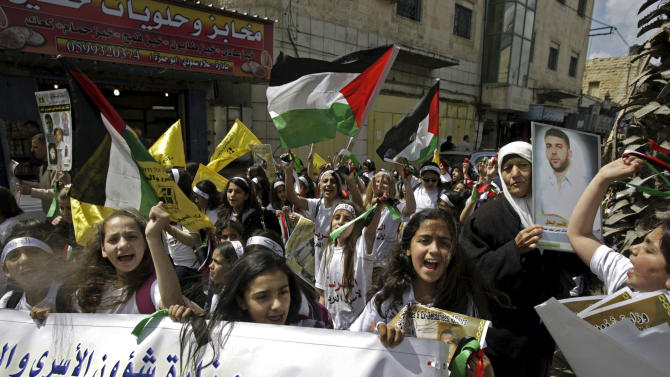 Palestinian students girls, chant slogans during a protest after Maysara Abu Hamdiyeh died in Israeli prison, in the West Bank city of Jenin, Thursday, April. 4, 2013. Demonstrations first erupted across the West Bank on Tuesday over the death of a Palestinian prisoner Abu Hamdiyeh who died from cancer. The prisoner, 64, was serving a life sentence for a 2002 foiled bombing of a busy Jerusalem cafe. (AP Photo/Mohammed Ballas).