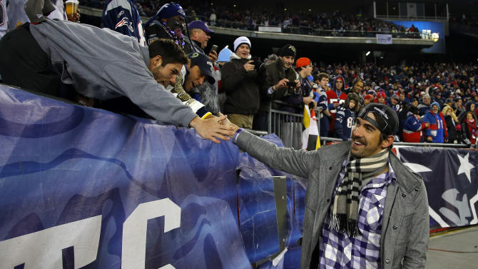 Former U.S. Olympic swimmer Michael Phelps speaks to a fan on the sidelines before the NFL football AFC Championship football game between the New England Patriots and the Baltimore Ravens in Foxborough, Mass., Sunday, Jan. 20, 2013. (AP Photo/Stephan Savoia)