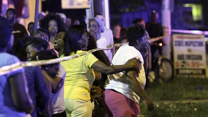 Family members react as they watch investigators at the scene of a fatal accident on Roosevelt Boulevard in the Olney section of Philadelphia on Tuesday evening July 16, 2013. Philadelphia police are investigating whether cars may have been drag racing when a mother and two young sons were struck and killed attempting to cross a busy highway. The woman's two other sons ages 4 and 5 are in critical condition. (AP Photo/ Joseph Kaczmarek)