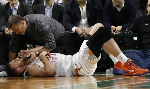 Phoenix Suns center Miles Plumlee is checked by a trainer after being injured during the second half of the Suns' 87-80 win over the Boston Celtics in an NBA basketball game in Boston Friday, Marc