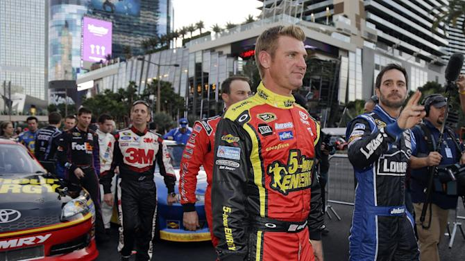 Clint Bowyer, left, and Jimmie Johnson walk down the Las Vegas Strip after driving in the Nascar Awards Week victory lap, Thursday, Nov. 29, 2012, in Las Vegas. (AP Photo/Julie Jacobson)