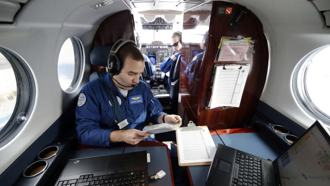 Lead Sensor Operator Andrew Halbach, left, checks the map as pilot Lt. Com. Scott Price looks over his shoulder during a National Oceanic and Atmospheric Administration flight to document coastal changes after Superstorm Sandy, Thursday, Nov. 1, 2012. (AP Photo/Alex Brandon)