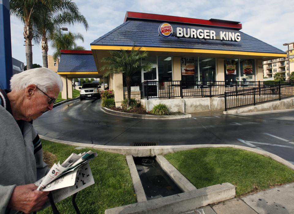 In this Thursday, April 25, 2013, photo, a pedestrian walks past a Burger King restaurant near downtown Los Angeles. Burger King reports their quarterly earnings on Friday, April 26, 2013. (AP Photo/Nick Ut)