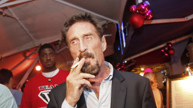 Anti-virus software founder John McAfee smokes a cigarrette as he walks on Ocean Drive in the South Beach area of Miami Beach, Fla., on his way to dinner Wednesday, Dec 12, 2012. McAfee arrived in the U.S. on Wednesday night after being deported from Guatemala, where he had sought refuge to evade police questioning in the killing of a man in neighboring Belize. (AP Photo/Alan Diaz)