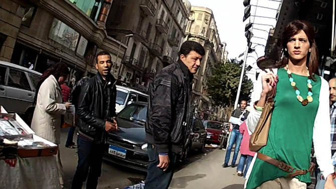 """In this undated image made from video released by the producers of """"Awel el Kheit,"""" or """"the Thread,"""" which aired in May 2013 on the private TV station ONTV, Waleed Hammad walks in a busy shopping district in Cairo, Egypt, dressed as a woman, as a hidden camera crew films him for an investigative story on sexual harassment. The 24-year-old actor dressed conservatively for his mission into the secret world of sexual harassment and abuse on the streets of Cairo, donning a long skirt and sleeved shirt and covering his head like many Egyptian women. (AP Photo/Courtesy of Awel el Kheit)"""