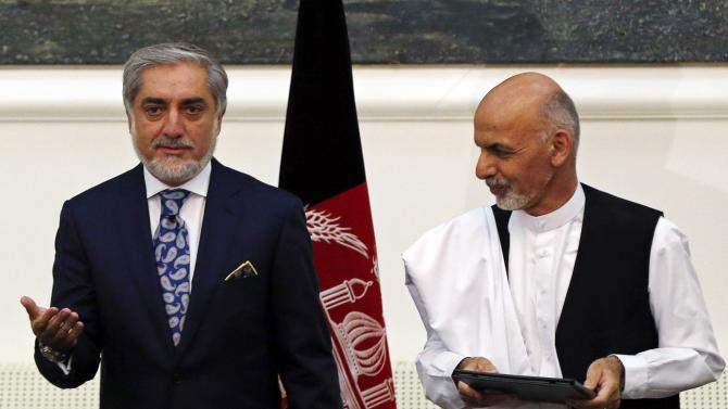 Afghan rival presidential candidates Abdullah and Ghani stand together after exchanging signed agreements for the country's unity government in Kabul