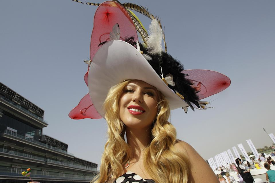 A woman poses for a photograph during the World Cup horse race at Meydan racecourse in Dubai, United Arab Emirates, Saturday, March 30, 2013. (AP Photo/Kamran Jebreili)