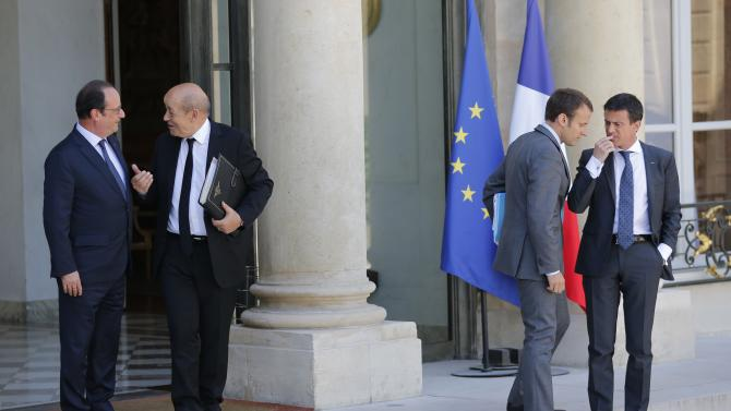 French President Hollande escorts Defence Minister Le Drian as Economy Minister Emmanuel Macron and Prime Minister Manuel Valls speak to each other as they leave the Elysee Palace following the weekly cabinet meeting in Paris