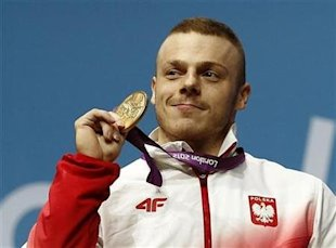 Poland's Adrian Edward Zielinski poses with his gold medal on the podium of the men's 85Kg weightlifting competition at the ExCel venue at the London 2012 Olympic Games