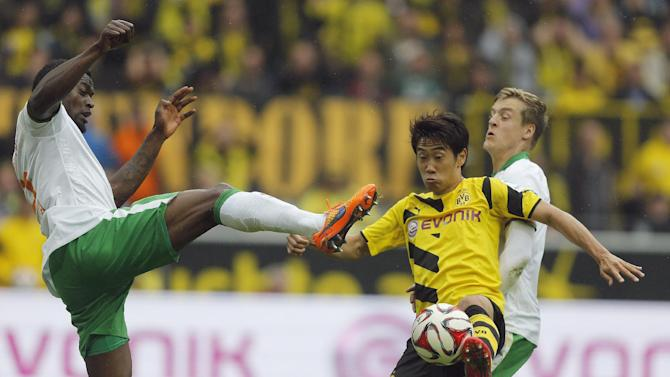 Bremen's Assani Lukimya from Congo, left, and Dortmund's Shinji Kagawa from Japan challenge for the ball during the German first division Bundesliga soccer match between BvB Borussia Dortmund  and SV Werder Bremen in Dortmund, Germany, Saturday, May 23, 2015. (AP Photo/Frank Augstein)