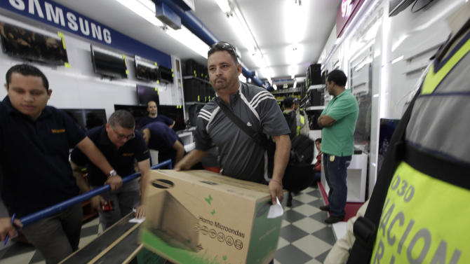 A shopper carries his newly-purchased microwave oven as he leaves an appliance store in Caracas, Venezuela, Wednesday, Nov. 13, 2013. President Nicolas Maduro in recent days ordered the military to take over appliance stores, slashing prices, leading bargain hunters to form block-long lines across the country. The populist measures seem designed to help Maduro's party get over the hump of next month's mayoral vote, its first electoral test since the president narrowly defeated opposition leader Henrique Capriles in April. But while the measures apparently are popular with voters, Maduro runs the risk of cannibalizing an already damaged economy.(AP Photo/Ariana Cubillos)
