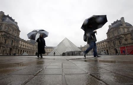 Two US tourists walk past the the Louvre Museum Pyramid's main entrance in Paris