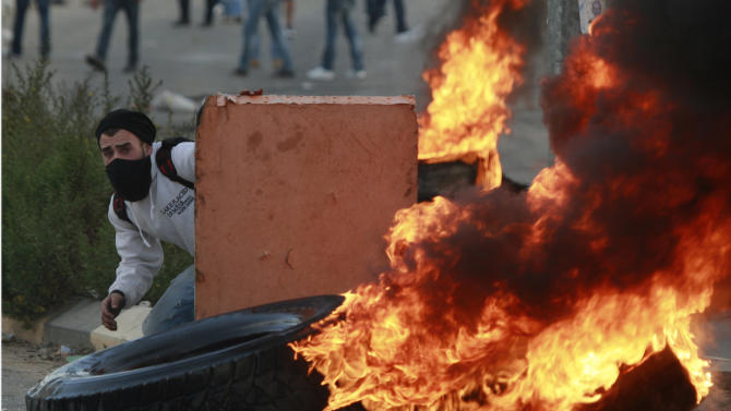 A Palestinian man hides during a protest against Israel's operations in Gaza Strip, outside Ofer, an Israeli military prison near the West Bank city of Ramallah, Sunday, Nov. 18, 2012. (AP Photo/Majdi Mohammed)