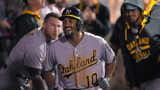 Oakland Athletics' Marcus Semien celebrates in the dugout after hitting a solo home run during the fourth inning of a baseball game against the Los Angeles Angels, Monday, April 20, 2015, in Los Angeles. (AP Photo/Mark J. Terrill)