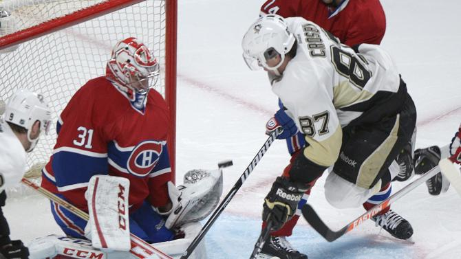 Montreal Canadiens goaltender Carey Price, left, makes a save against Pittsburgh Penguins' Sidney Crosby during the second period of an NHL hockey game Saturday, March 2, 2013, in Montreal. (AP Photo/The Canadian Press, Graham Hughes)