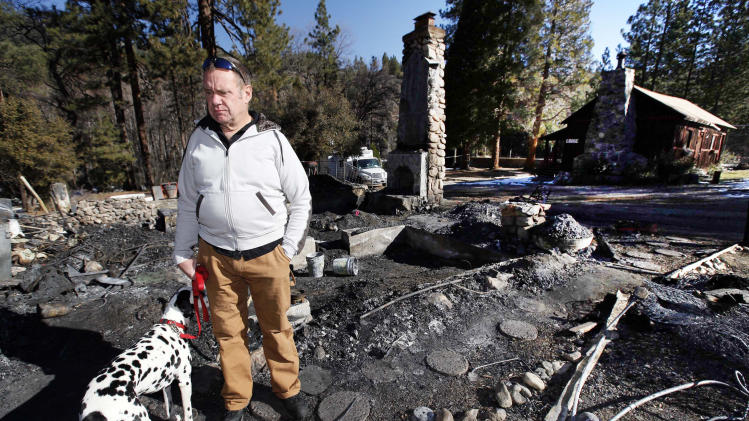 FILE - In this Friday Feb. 15, 2013 file photo, Rick Heltebrake with his dog Suni looks over the burned-out cabin where Christopher Dorner's remains were found after a police standoff Tuesday near Big Bear, Calif. Dorner took his pickup during his escape attempt. Heltebrake, a ranger who takes care of a Boy Scout camp, was checking the perimeter of the camp for anything out of the ordinary when he saw Dorner emerge from behind some trees. (AP Photo/Nick Ut, FIle)