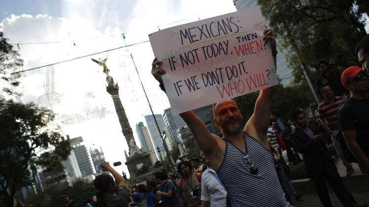 A demonstrator holds up a placard during a march against the radical reform of the country's energy market in downtown Mexico City