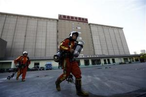 Rescuers walk inside a refrigeration unit of Shanghai Weng's Cold Storage Industrial Co. Ltd., in the Baoshan district of Shanghai