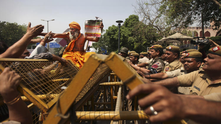 An Indian Hindu holy man shouts slogans as he sits on police barricades outside Delhi Police headquarters during a protest against the rape of a 5-year-old girl in New Delhi, India, Saturday, April 20, 2013. Officials say the child is in serious condition after being raped and tortured by a man who held her in a locked room in India's capital for two days. Police say the girl went missing Monday and was found Wednesday by neighbors who heard her crying in a room in the same New Delhi building where she lives with her parents. (AP Photo/Altaf Qadri)