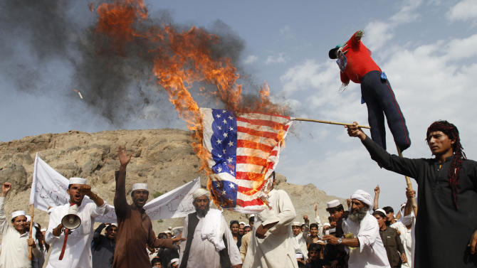 Afghans burn the U.S. flag in Ghanikhel district of Nangarhar province, east of Kabul, Afghanistan, Friday, Sept. 14, 2012 during a protest against an anti-Islam film which depicts the Prophet Muhammad as a fraud, a womanizer and a madman. (AP Photo/Rahmat Gul)