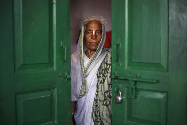 A widow poses for a picture inside her room at the Meera Sahavagini ashram