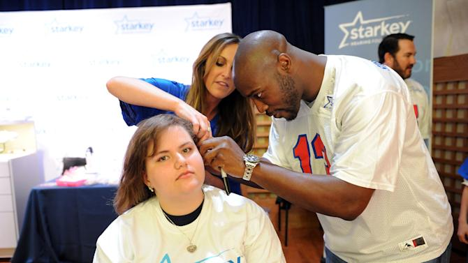 Deanna Light gets fitted with a new hearing aid from Starkey Hearing Foundation with the help of Dr. Trevi Sawalich and Tennessee Titan Will Witherspoon on Saturday, Feb. 2, 2013 in New Orleans. (Photo by Cheryl Gerber/Invision for Starkey Hearing Foundation/AP Images)