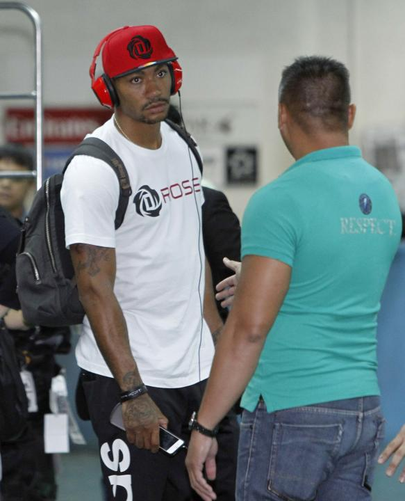 NBA star Derrick Rose listens to a security officer as he waits for his colleagues after arriving for his Asia tour, at the Manila International Airport