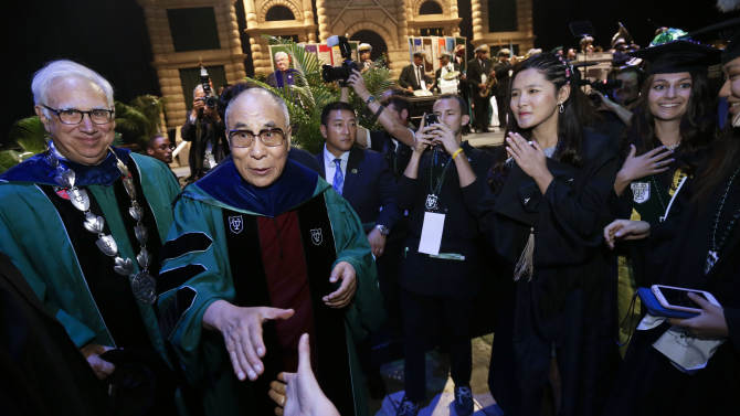 The Dalai Lama walks into the crowd to greet graduates after delivering the commencement address at Tulane University's 179th commencement ceremony at the Mercedes-Benz Superdome in New Orleans on Saturday, May 18, 2013. (AP Photo/Gerald Herbert)
