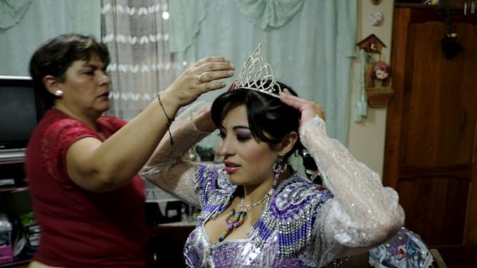 Alicia Vargas, 23, a performer from the Urus Diablada group, is helped by her mother to dress  before a practice ahead of Carnival in Oruro