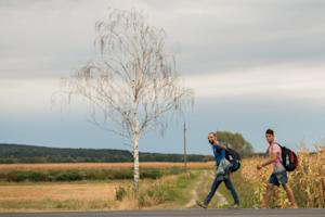 Migrants make their way along a road after crossing…