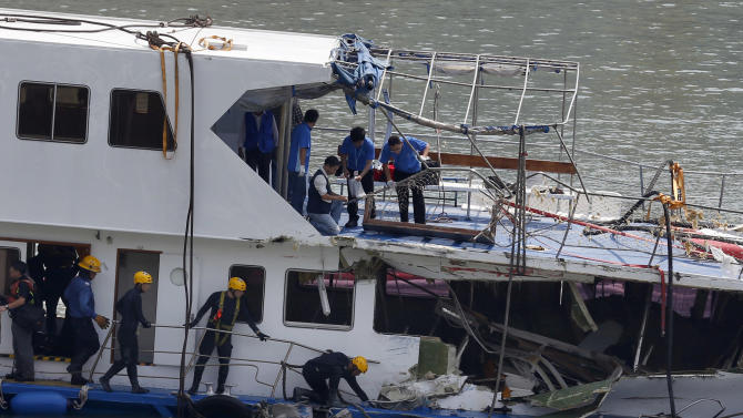 A group of firemen and police officers investigate on a salvaged boat which sank after colliding with a ferry near Lamma Island, off the southwestern coast of Hong Kong Island Wednesday, Oct. 3, 2012. An official with the ferry company involved in the collision that killed 38 people said Wednesday that the vessel recently passed inspection, but he had no details about how the crash occurred.(AP Photo/Kin Cheung)