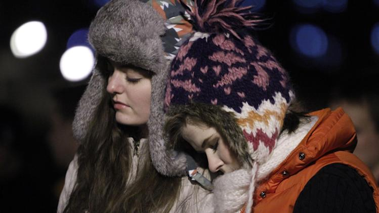 Virginia Tech freshmen, Massie Cashion, left, and Kasey Kraft, both from Alexandria, Va., participate in an impromptu candlelight vigil in front of the 4/16 memorial on the campus of Virginia Tech after two shootings on the campus in Blacksburg, Va., Thursday, Dec. 8, 2011. A gunman killed a police officer and then apparently shot himself to death nearby in a baffling attack that shook up the campus nearly five years after it was the scene of the deadliest shooting rampage in modern U.S. history.  (AP Photo/Steve Helber)