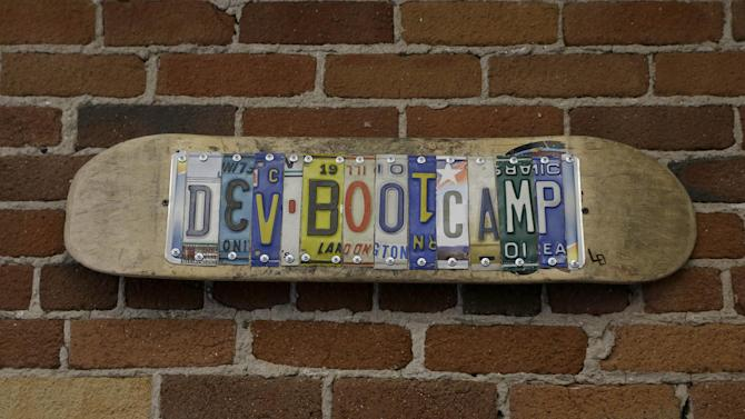 "A sign for Dev Bootcamp is shown at their office in San Francisco, Tuesday, April 2, 2013. Dev Bootcamp is one of a new breed of computer-programming schools that's proliferating in San Francisco and other U.S. tech hubs. These ""hacker boot camps"" promise to teach students how to write code in two or three months and help them get hired as web developers, with starting salaries between $80,000 and $100,000, often within days or weeks of graduation. (AP Photo/Jeff Chiu)"